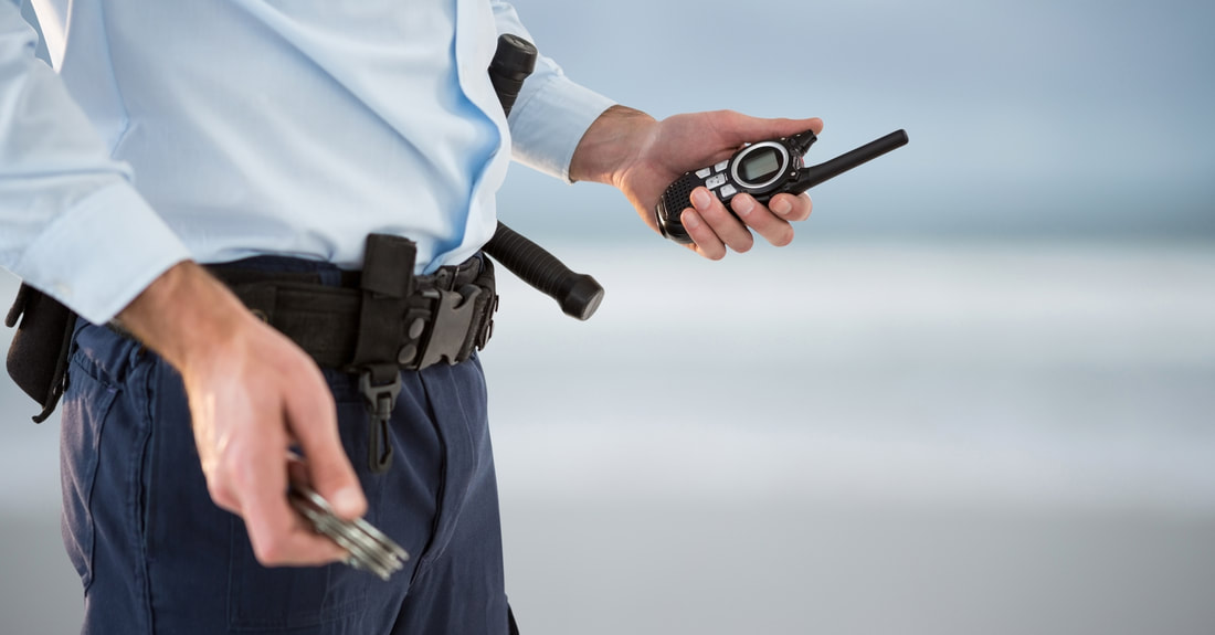 Picture of a security guard with a walkie-talkie in one hand and a set of hand-cuffs in the other.
