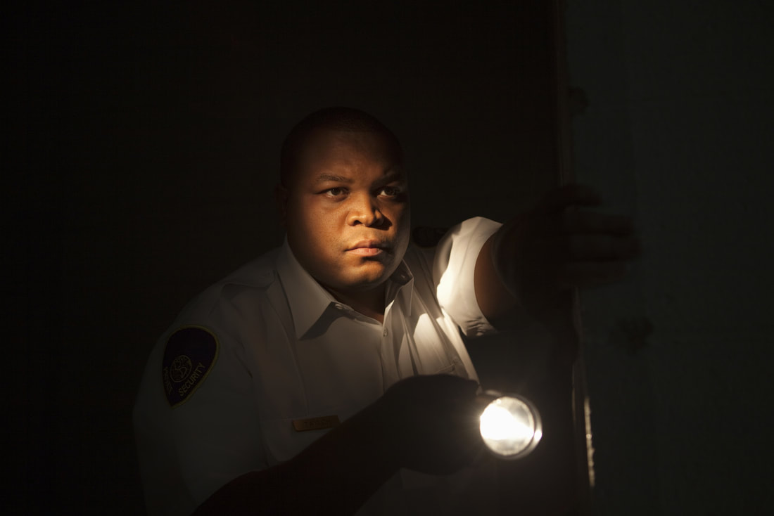Picture of a security guard with a flashlight making an inspection tour of the complex he is guarding.