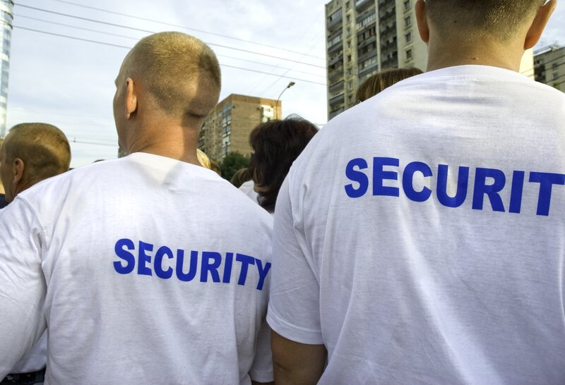 Picture looking at the backs of two security guard personnel with a crowd in the background