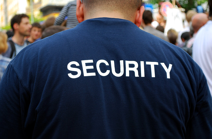 Picture of the back of a security guard working a special event with crowded streets.