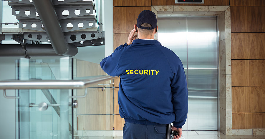Picture of and unarmed security guard watching an elevator waiting for someone to exit.