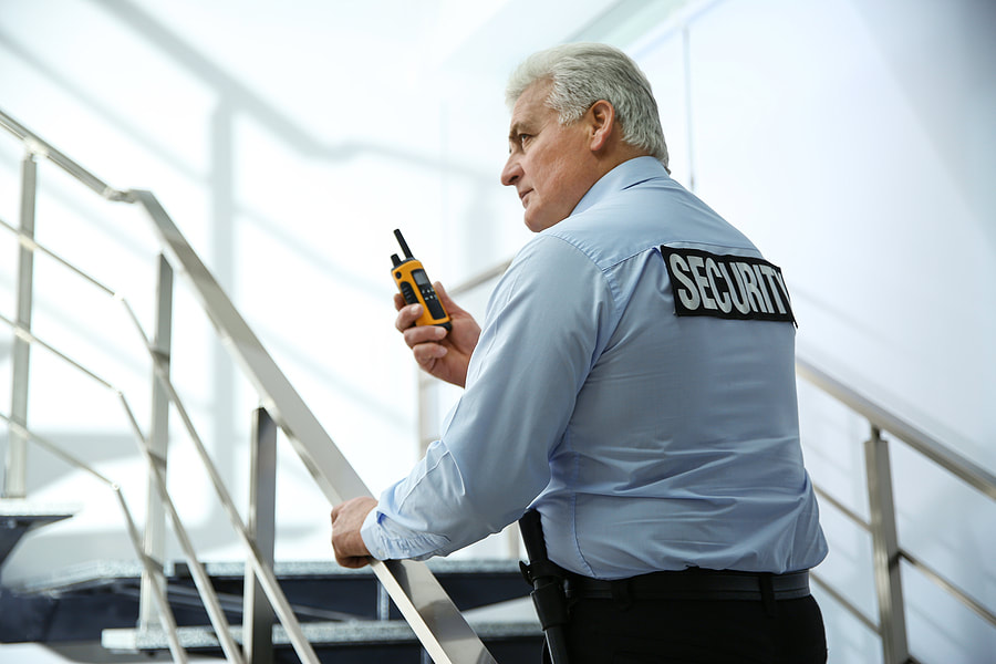 Picture of a security guard walking up a set of stairs with a walkie-talkie in his hand while making an inspection tour during his shift in an office complex..